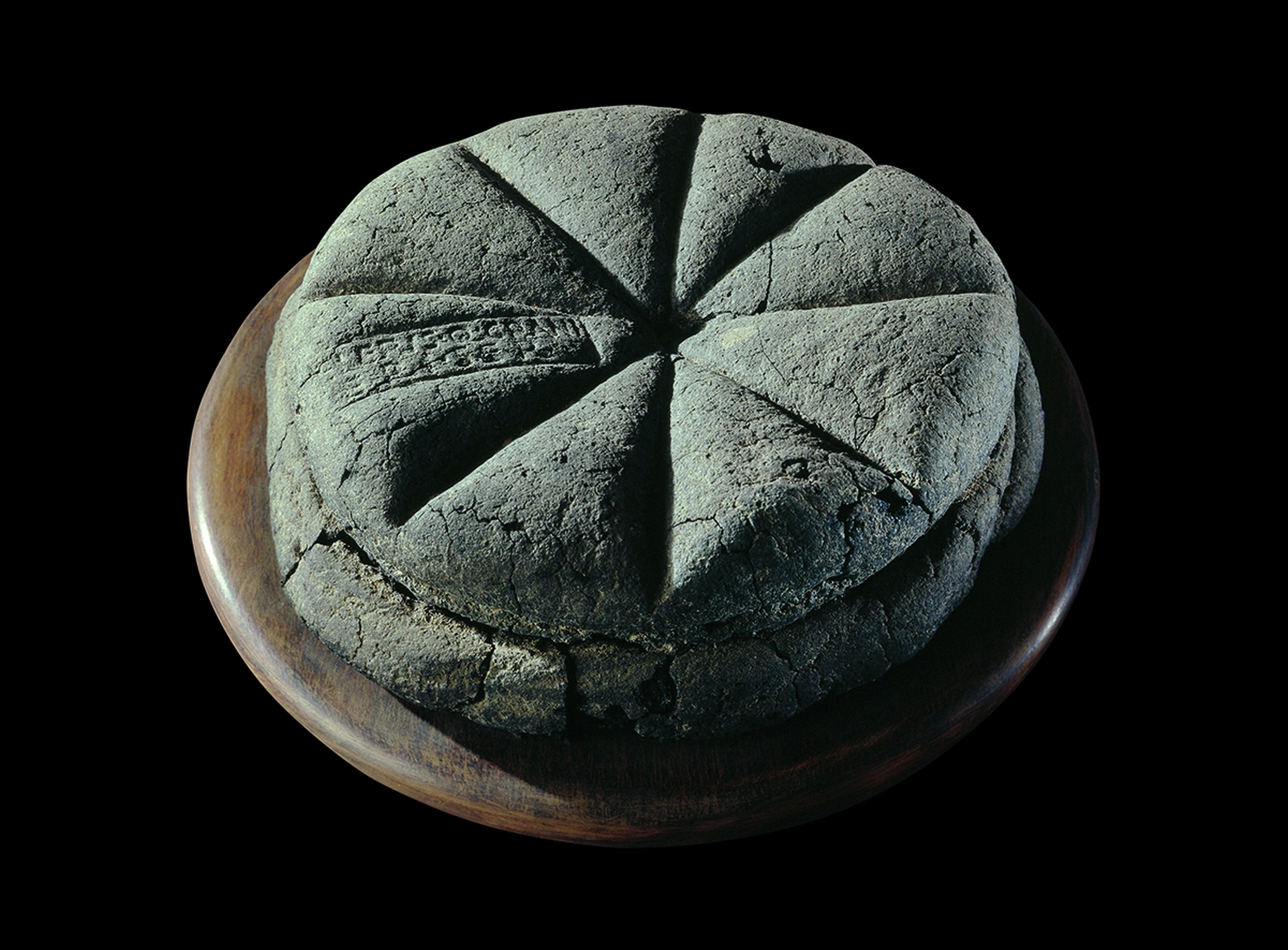Fig. 3: A carbonised loaf of bread with the stamp 'Property of Celer, Slave of Q. Granius Verus', Herculaneum, House of the Stags, AD 79, Museo Archeologico Nazionale di Napoli, © Fotografica Foglia (Naples).