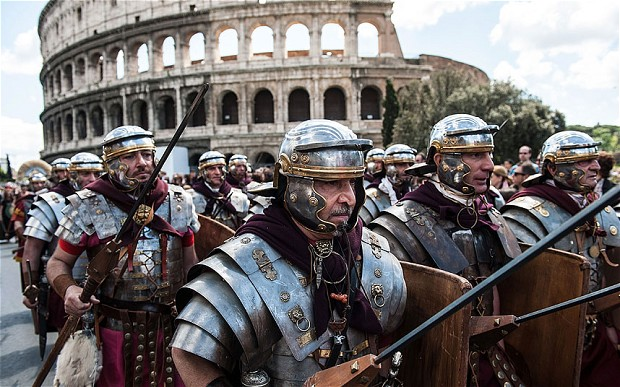 Actors dressed as Roman soldiers marching in front of the Coliseum, Rome (Courtesy of the Telegraph  Company, UK)